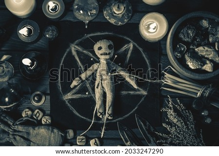 Voodoo Magic concept. Voodoo doll studded with needles with pierced rag heart on pentagram and around burning candles. Spooky or eerie magical esoteric ritual, black and white photo Stock fotó ©