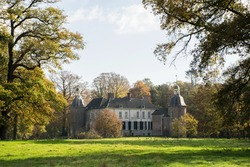 Vorden, Gelderland/Netherlands: Castle in autumn landscape with large trees and meadow. Dutch old estate monumental building in fall natural park. Historic locations.