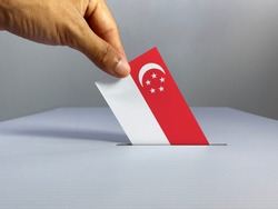 Voting / election concept: hand holding voting card with country national flag, inserting it into white ballot box; clean neutral background — Singapore