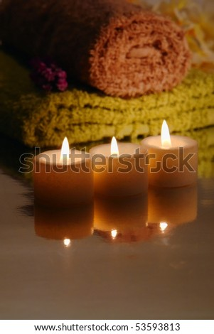 Votive candles burning with a soft glow with towels in a spa