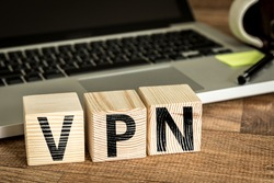 VPN (Virtual Private Network) written on a wooden cube in front of a laptop