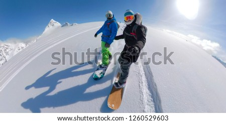 VR 360: Young couple on fun active winter vacation in stunning British Columbia snowboarding together off piste on a sunny day. Extreme male and female heliboarders shredding the pristine powder snow.