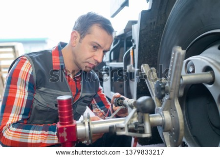 vulcanizing shop worker removing the vehicles wheel #1379833217