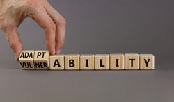 Vulnerability or adaptability symbol. Businessman turns wooden cubes and changes words 'vulnerability' to 'adaptability'. Grey background, copy space. Business, vulnerability or adaptability concept.