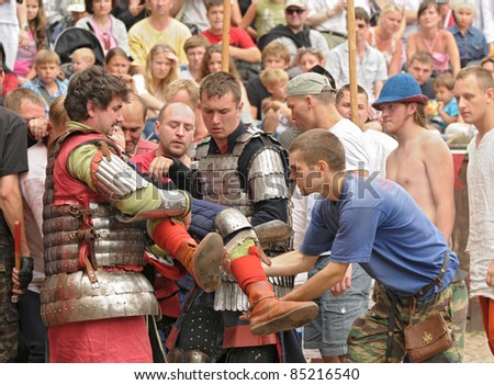 "VYBORG, RUSSIA - JULY 31: Unidentified men in a knightly armor bear the traumatized fighter during festival ""Knight's castle"" carrying out on July 31, 2011 in Vyborg, Russia."
