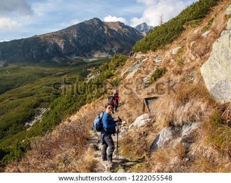 Vysoke Tatry, Slovakia - October 9, 2018: Hikers on trail at Great Cold Valley,  Vysoke Tatry (High Tatras), Slovakia. The Great Cold Valley is 7 km long valley, very attractive for tourists #1222055548