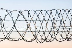 W rapped barbed wire fence with spikes and sky in the background. Rusted chain link fence guarding high security facility like airport, jail or country boarder