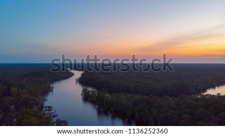 Waccamaw waterway on a Sunday evening surrounded by trees with an orange sunset and boats.