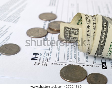 Wad of american dollars and coins on W-9 income tax forms Zdjęcia stock ©