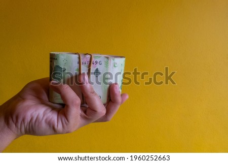 wad of Argentine money or bills in a man's hand in a way that looks like he is receiving it Photo stock ©