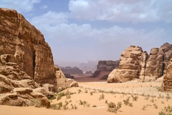 Wadi Rum desert, Jordan, Middle East, The Valley of the Moon. Orange sand, haze, clouds. Designation as a UNESCO World Heritage Site. National park outdoors landscape. Offroad adventures travel.