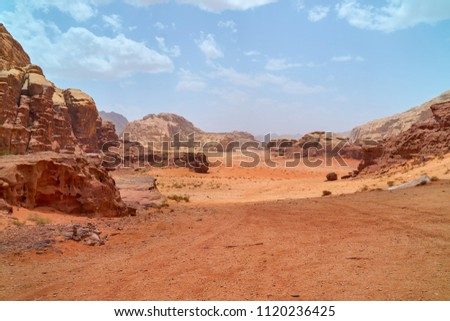 Wadi Rum desert, Jordan, The Valley of the Moon. Orange sand, haze, clouds. Designation as a UNESCO World Heritage Site. Red planet Mars  landscape. Offroad adventures travel background.               #1120236425