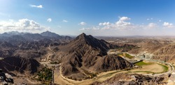 Wadi Shawka Dam panorama, with empty dam, dry riverbed and rocky Hajar Mountains, United Arab Emirates.