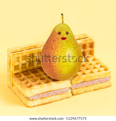 Wafers with blueberry souffle in form of sofa and pear. Minimalist style. Creative idea, imagination and fantasy. Attraction of attention to the problems of physical inactivity and abuse of sweet