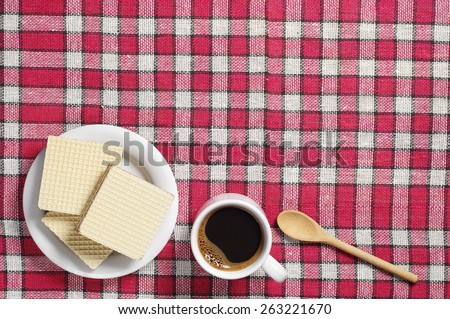 Wafers with chocolate and cup of hot coffee on table covert red tablecloth, top view