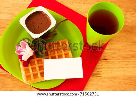 Waffle, chocolate mousse and juice, decorated with flowers and blank ticket placed on plate.