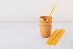 Waffle coffee cups and pasta straws on neutral background with copy space. Zero waste, plastic free, stop pollution, ecological concept