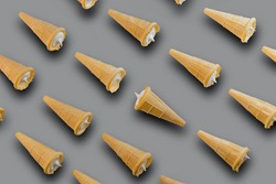 Waffle cones with white filling on a gray background. Sweet waffle cones with filling. The image of a sweet treat.