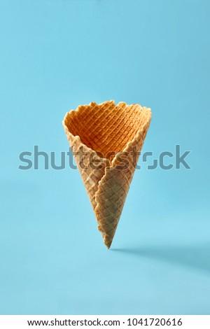 Waffle cornet on light blue background.