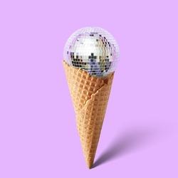 Waffle cornet with disco ball isolated on purple