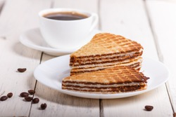 waffle sandwiches with boiled condensed milk in plate on white wooden table with cup of coffee. closeup.