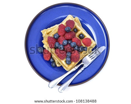 Waffles with fresh raspberries and blueberries on blue plate, overhead view - stock photo