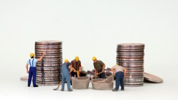 Wage and labor concept. Miniature workers working with piles of coins.