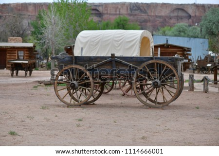 wagon (covered and uncovered) in front of  log cabins. all original to bluff fort in utah. established in 1880