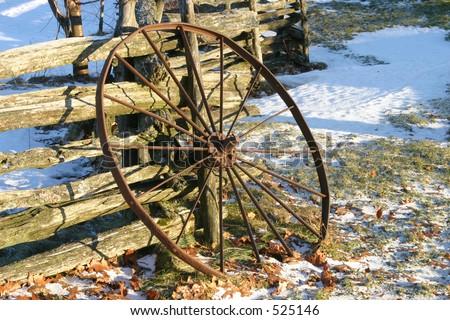 Rueda del carro que se inclina en la cerca de madera delcarril