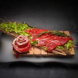 Wagyu beef slice on dark background.
