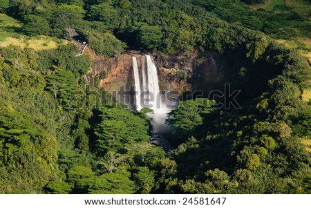 Wailua waterfall taken from the air and surrounded by trees on Kauai