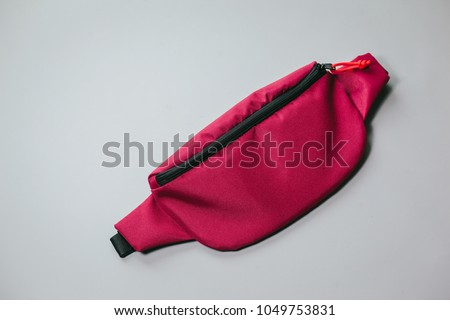 Waist bag of banana of red colour on a white background isolation #1049753831