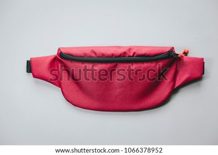Waist bag of banana of red colour on a white background isolation