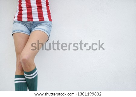 4300e55364 Waist down cut off of slim young woman in strippy top and knee socks on  white
