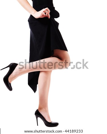 Waist-down view of woman's legs in black high heels. She is standing on one leg against white background, while pinching her black dress up.