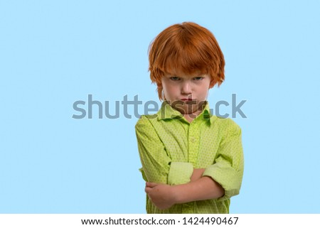 Waist up emotional portrait of redhead boy wearing green shirt on a blue background with copy space in the studio. Hi standing arms crossed and looking angrily at the camera  Stock foto ©