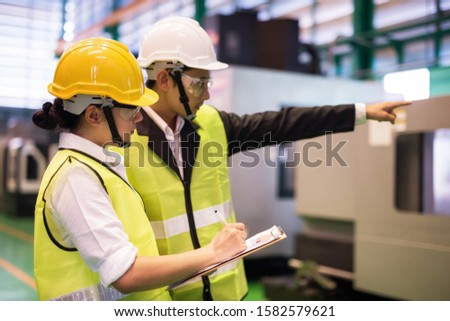 Waist up female factory worker write implement audit result of industrial machine while manager point finger to machinery. Manufacturing industry to produce car spare parts. Quality assurance (QA). Stock foto ©