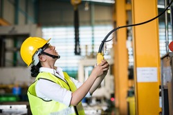 Waist up female worker uses remote control panel to lift up or down of power trolley crane in factory warehouse. Asian woman controls crane beam in manufacturing facility.