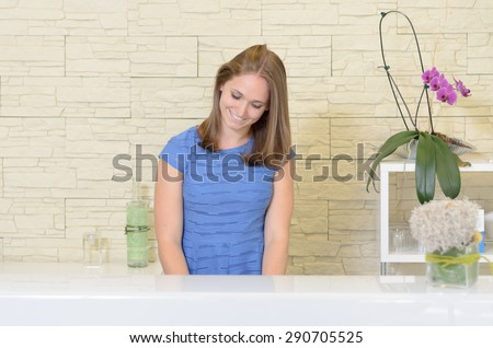 Waist up front view of elegant young 20s woman with light brown hair standing behind white counter in spa or beauty salon wearing blue top smiling and looking down, purple orchid plant in foreground