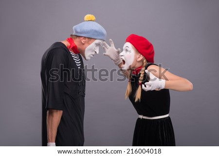 Waist-up horizontal portrait of couple of two mimes standing face to face and screaming on each other, male mime very angry isolated on grey background with copy place