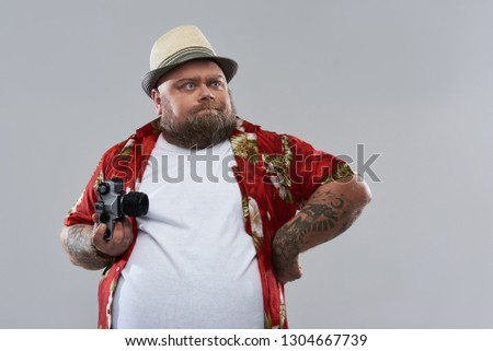 d16ef178d Waist up isolated on grey background photo of tourist in Hawaiian shirt  holding retro camera and