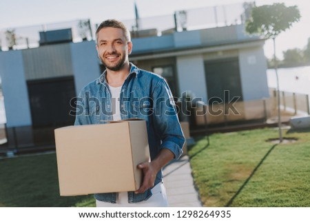 Waist up of a smiling handsome man standing near his house while carrying a paper box