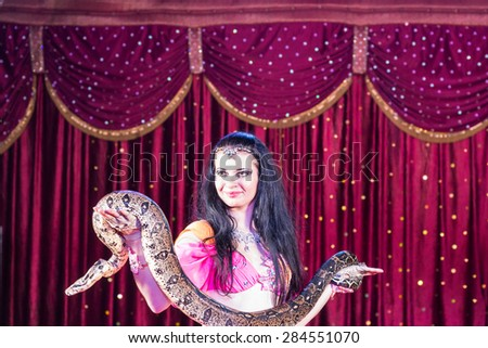Waist Up of Exotic Dark Haired Belly Dancer Standing on Stage Holding Large Snake with Red Curtain in Background
