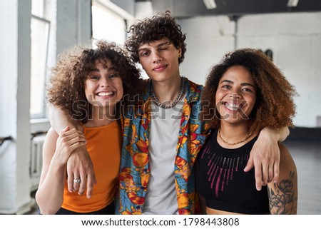 Waist up of happy three friends standing together and looking at camera while smiling in studio Foto stock ©
