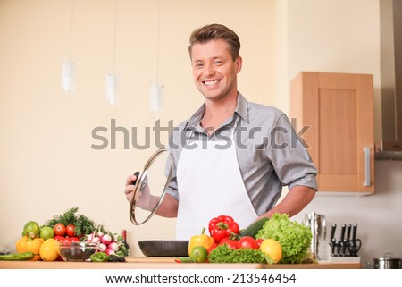 waist up of man holding frying pan lid. guy preparing healthy food at kitchen