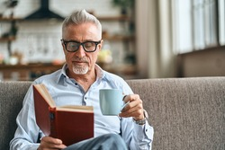 Waist up of mature man reading book while sitting on sofa in his living room and holding cup of coffee. Domestic lifestyle concept. Copy space