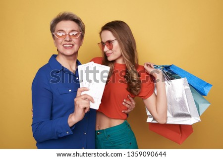 Waist up of pretty Caucasian ladies wearing fashionable blouses after shopping. Pretty daughter holding colorful paper bags in arm while her cheerful mother keeping two tickets against orange