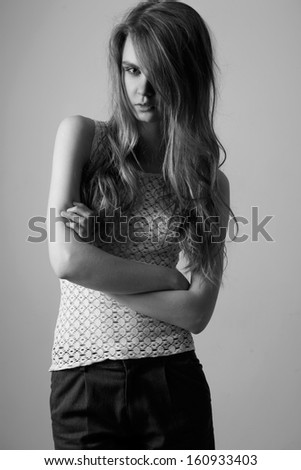 Waist up of pretty woman with beauty long hair, natural make-up and crossed hands,dressed in white T-shirt and dark grey shorts,  looking at camera. Black and White photo