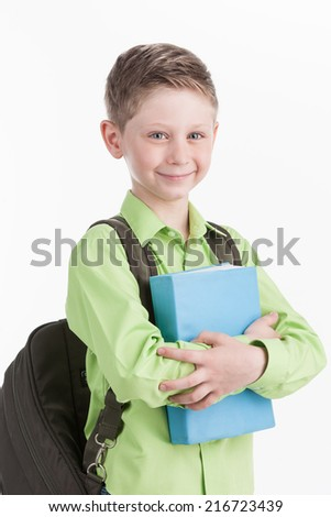 waist up of schoolboy with backpack, isolated on white background. boy holding blue book and smiling