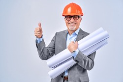 Waist up of smiling adult architect in jacket showing thumb up, isolated on blue background. Construction concept